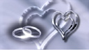 Royalty Free Video of Silver Rotating Hearts and Wedding Rings