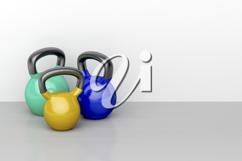 Three kettlebells of different size on shiny gray floor in the fitness center