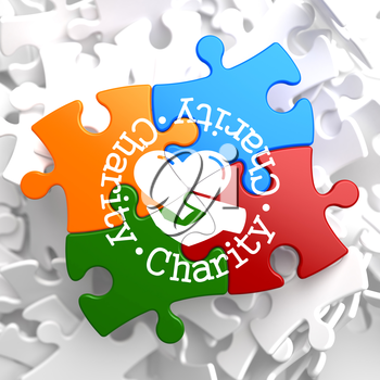 Charity Word Written Arround Icon of Heart in the Hand, Located on Multicolor Puzzle. Social Concept.