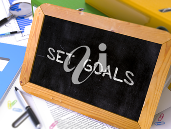 Set Goals Handwritten on Chalkboard. Composition with Small Chalkboard on Background of Working Table with Ring Binders, Office Supplies, Reports. Blurred Background. Toned Image. 3D Render.
