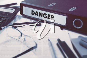 Danger - Office Folder on Background of Working Table with Stationery, Glasses, Reports. Business Concept on Blurred Background. Toned Image.