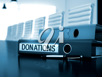 Donations. Business Illustration on Blurred Background. Office Binder with Inscription Donations on Table. Donations - Illustration. Donations - Folder on Working Wooden Table. Toned Image. 3D Render.