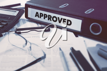 Approved - Office Folder on Background of Working Table with Stationery, Glasses, Reports. Business Concept on Blurred Background. Toned Image.