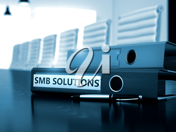 File Folder with Inscription SMB Solutions on Working Office Desktop. SMB Solutions - File Folder on Wooden Desktop. SMB Solutions - Business Concept on Blurred Background. 3D.