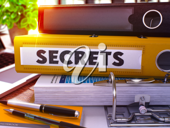 Yellow Office Folder with Inscription Secrets on Office Desktop with Office Supplies and Modern Laptop. Secrets Business Concept on Blurred Background. Secrets - Toned Image. 3D.
