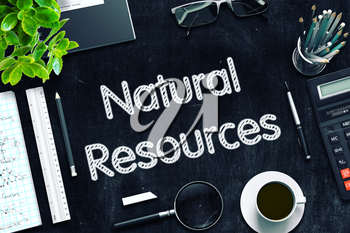 Natural Resources. Business Concept Handwritten on Black Chalkboard. Top View Composition with Chalkboard and Office Supplies. 3d Rendering. Toned Illustration.