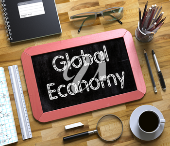 Global Economy on Small Chalkboard. Red Small Chalkboard with Handwritten Business Concept - Global Economy - on Office Desk and Other Office Supplies Around. Top View. 3d Rendering.