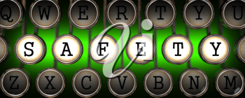 Safety Concept on Old Typewriter's Keys on Green Background.