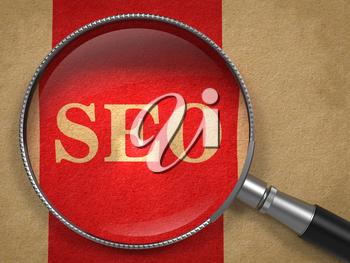 SEO Inscription Through a Magnifying Glass on a Red Background.