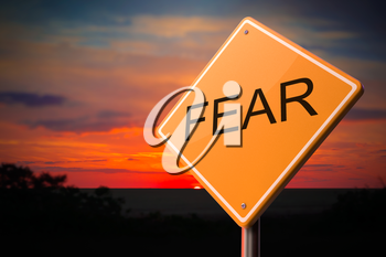 Fear on Warning Road Sign on Sunset Sky Background.