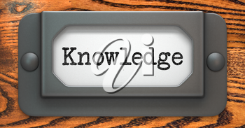 Knowledge Inscription on File Drawer Label on a Wooden Background.