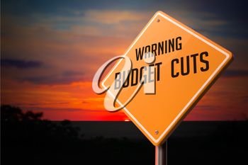Budget Cuts on Warning Road Sign on Sunset Sky Background.