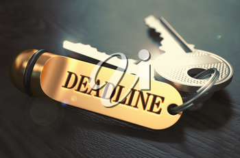 Keys and Golden Keyring with the Word Deadline over Black Wooden Table with Blur Effect. Toned Image.
