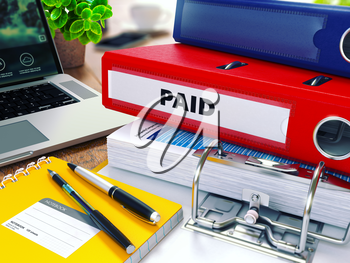 Paid - Red Ring Binder on Office Desktop with Office Supplies and Modern Laptop. Business Concept on Blurred Background. Toned Illustration.
