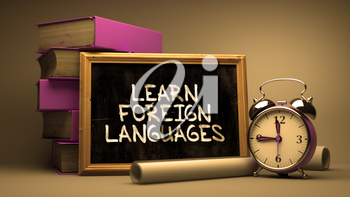 Learn Foreign Languages Handwritten on Chalkboard. Time Concept. Composition with Chalkboard and Stack of Books, Alarm Clock and Scrolls on Blurred Background. Toned Image.