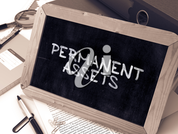 Permanent Assets - Chalkboard with Hand Drawn Text, Stack of Office Folders, Stationery, Reports on Blurred Background. Toned Image.