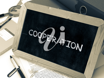 Cooperation - Chalkboard with Hand Drawn Text, Stack of Office Folders, Stationery, Reports on Blurred Background. Toned Image.