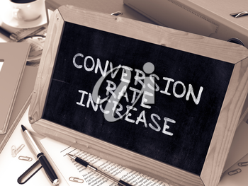 Conversion Rate Increase - Chalkboard with Hand Drawn Text, Stack of Office Folders, Stationery, Reports on Blurred Background. Toned Image.
