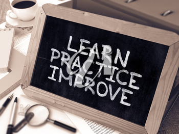 Learn, Practice, Improve. Handwritten by white Chalk on a Blackboard. Composition with Small Chalkboard on Working Table with Office Folders, Stationery, Reports. Blurred, Toned Image.