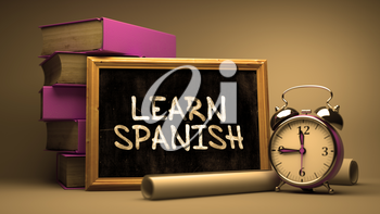 Learn Spanish Concept Hand Drawn on Chalkboard. Blurred Background. Toned Image.