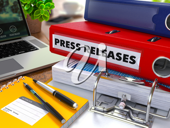 Red Ring Binder with Inscription Press Releases on Background of Working Table with Office Supplies, Laptop, Reports. Toned Illustration. Business Concept on Blurred Background.