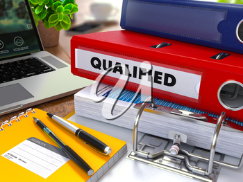 Red Ring Binder with Inscription Qualified on Background of Working Table with Office Supplies, Laptop, Reports. Toned Illustration. Business Concept on Blurred Background.