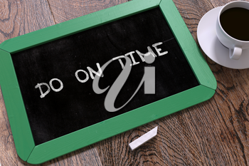 Handwritten Do on Time on a Green Chalkboard. Top View Composition with Chalkboard and White Cup of Coffee.