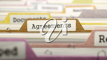 File Folder Labeled as Agreements in Multicolor Archive. Closeup View. Blurred Image.