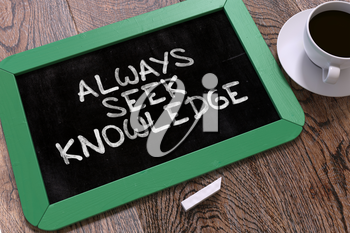 Always Seek Knowledge - Inspirational Quote Hand Drawn on Green Chalkboard on Wooden Table. Business Background. Top View.