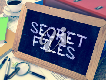 Secret Files Concept Hand Drawn on Chalkboard on Working Table Background. Blurred Background. Toned Image.