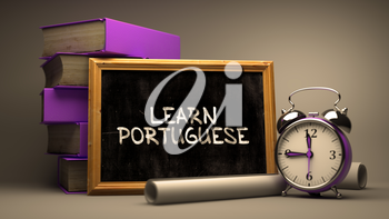 Learn Portuguese - Chalkboard with Hand Drawn Inspirational Quote, Stack of Books, Alarm Clock and Rolls of Paper on Blurred Background. Toned Image.
