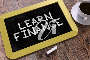 Learn Finance - Yellow Chalkboard with Hand Drawn Inspirational Quote and White Cup of Coffee on Wooden Table. Top View.