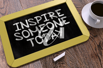 Inspire Someone Today - Motivation Quote Handwritten on Yellow Chalkboard. Business Concept. Composition with Chalkboard and Cup of Coffee. Top View Image.