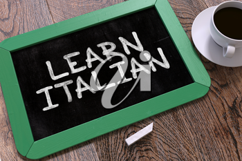 Learn Italian - Green Chalkboard with Hand Drawn Text and White Cup of Coffee on Wooden Table. Top View.