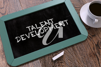 Talent Development Handwritten on Blue Chalkboard. Business Concept. Composition with Chalkboard and Cup of Coffee. Top View Image.