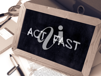 Act Fast Handwritten by white Chalk on a Blackboard. Composition with Small Chalkboard on Background of Working Table with Office Folders, Stationery, Reports. Blurred, Toned Image.