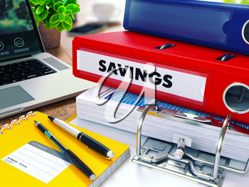 Savings - Red Ring Binder on Office Desktop with Office Supplies and Modern Laptop. Business Concept on Blurred Background. Toned Illustration.