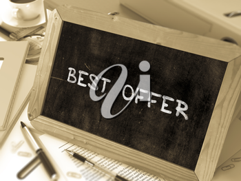 Best Offer Handwritten by White Chalk on a Blackboard. Composition with Small Chalkboard on Background of Working Table with Office Folders, Stationery, Reports. Blurred Background. Toned Image.
