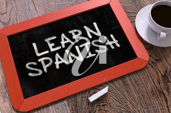 Learn Spanish Concept Hand Drawn on Red Chalkboard on Wooden Table. Business Background. Top View.