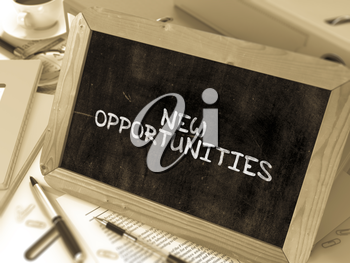 New Opportunities - Chalkboard with Hand Drawn Text, Stack of Office Folders, Stationery, Reports on Blurred Background. Toned Image.