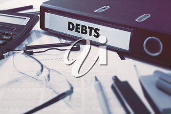 Debts - Office Folder on Background of Working Table with Stationery, Glasses, Reports. Business Concept on Blurred Background. Toned Image.