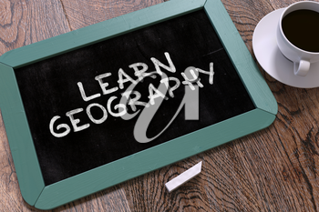 Learn Geography Handwritten on Blue Chalkboard. Business Concept. Composition with Chalkboard and Cup of Coffee. Top View Image. 3d Render.