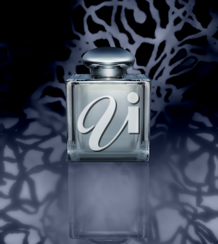 Glass bottle of perfume on a dark gray background.