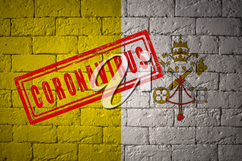 Flag of the Vatican City on brick wall texture. stamped of Coronavirus. Corona virus concept. On the verge of a COVID-19 or 2019-nCoV Pandemic. Novel Chinese Coronavirus outbreak