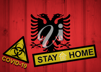 Flag of the Albania in original proportions. Quarantine and isolation - Stay at home. flag with biohazard symbol and inscription COVID-19.