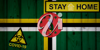 Flag of the Dominica in original proportions. Quarantine and isolation - Stay at home. flag with biohazard symbol and inscription COVID-19.