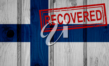 flag of Finland that survived or recovered from the infections of corona virus epidemic or coronavirus. Grunge flag with stamp Recovered