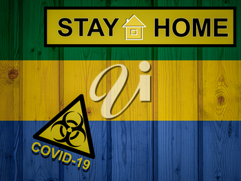 Flag of the Gabon in original proportions. Quarantine and isolation - Stay at home. flag with biohazard symbol and inscription COVID-19.