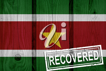 flag of Suriname that survived or recovered from the infections of corona virus epidemic or coronavirus. Grunge flag with stamp Recovered
